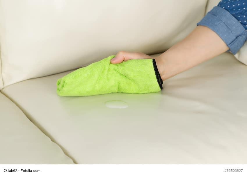 Mikrofiber-Tuch wird über einem Fleck auf einem hellen Sofa gehalten