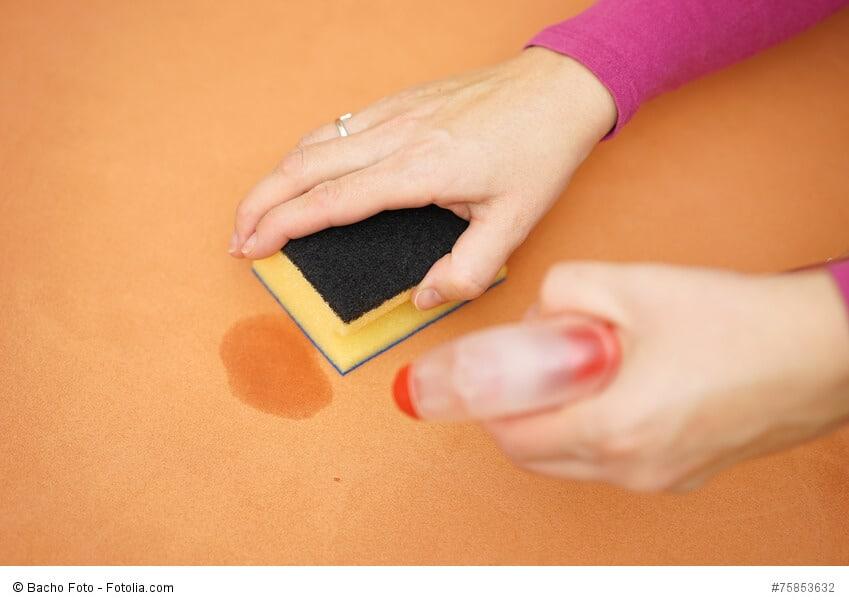 Orange-farbener Untergrund wird mit Schwamm und Reiniger gesäubert